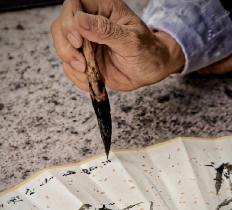 Old Hand holding a brush while writing Chinese caligraphy